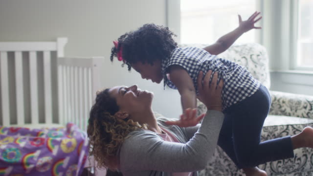 vidéos et rushes de mother and daughter playing in bedroom. - enfant