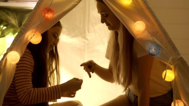 vídeos y material grabado en eventos de stock de madre e hija jugando en la tienda de campaña. concepto del día de la madre. - tienda de campaña