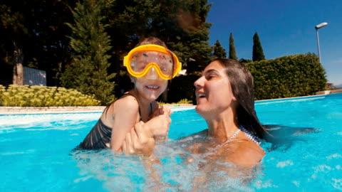 stockvideo's en b-roll-footage met moeder en dochter spelen in het zwembad van het resort - babymeisjes