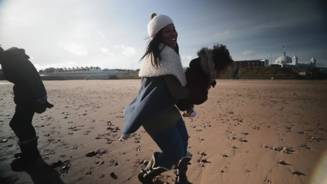 mother and daughter playing on the beach - whitley bay stock videos & royalty-free footage