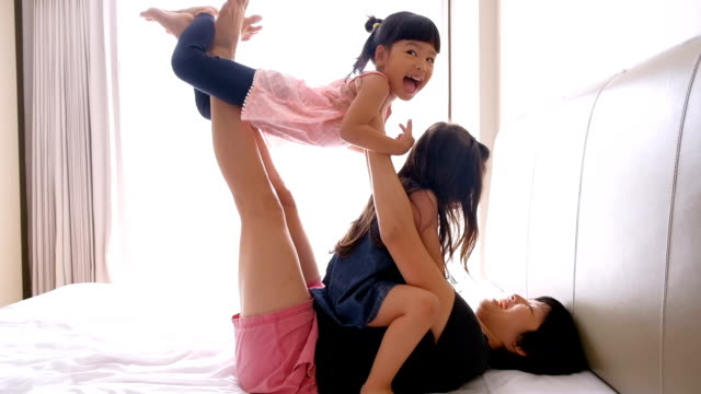 mother and daughter playing on the bed - single mother stock videos & royalty-free footage