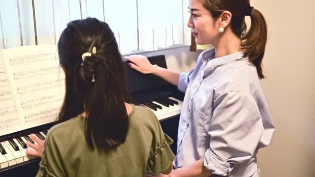 ピアノを弾く母と娘。 - hobbies点の映像素材/bロール