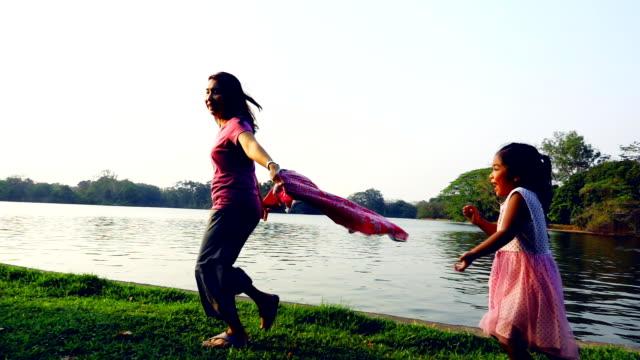 公園で追いかけてスーパー SLO MO 母と娘プレイを実行しています。