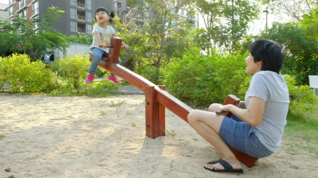 Mother and Daughter playing seesaw at playground