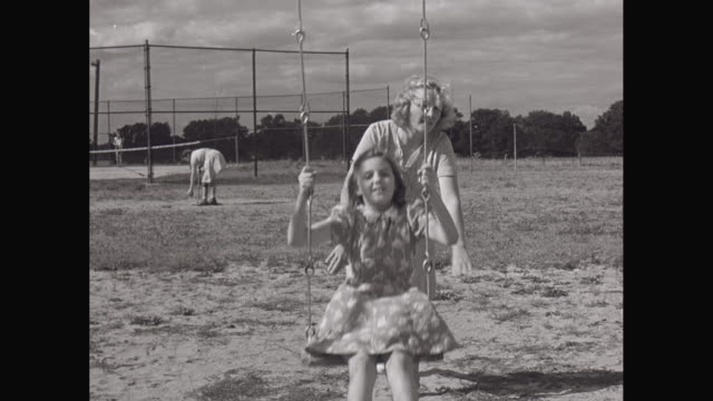 MS Mother and daughter playing swing in playground / United States