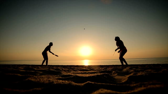 mother and daughter playing tennis on beach at sunset - racket stock videos and b-roll footage
