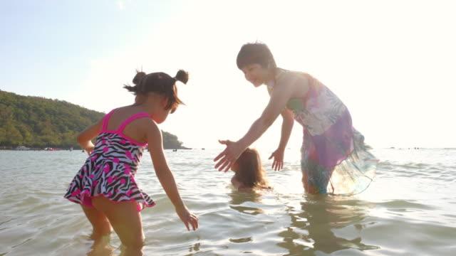 vídeos de stock, filmes e b-roll de mãe e filha brincando no mar - família de dois filhos