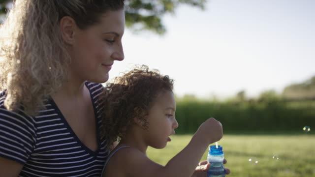 vídeos y material grabado en eventos de stock de madre e hija jugando juntos afuera - de descendencia mixta