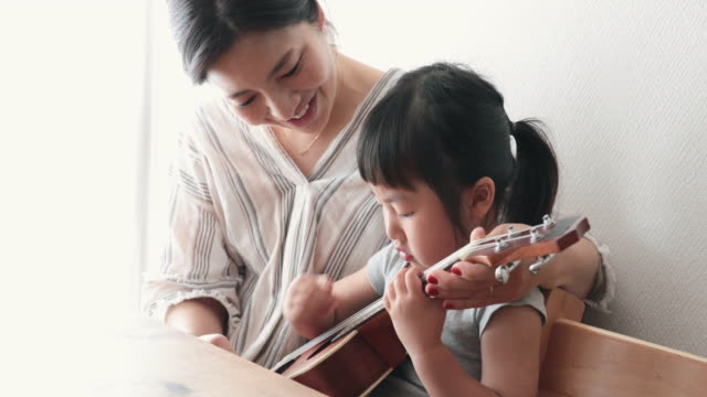 vídeos de stock, filmes e b-roll de mãe e filha jogando ukulele em casa - ukulele