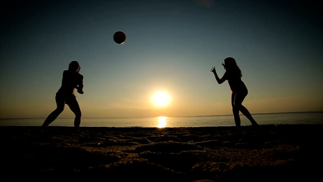 mother and daughter playing volleyball on the beach at sunset - bikini stock videos and b-roll footage