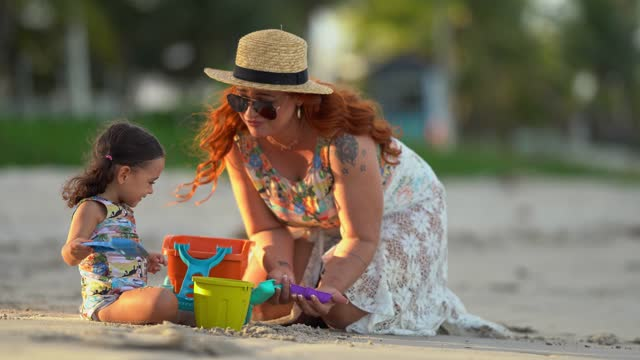 mother and daughter playing with beach sand - swimming costume stock videos & royalty-free footage