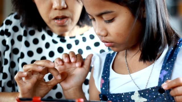 stockvideo's en b-roll-footage met mother and daughter playing with electronic tablet in cafe - elektronische organiser