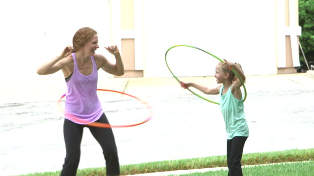 mother and daughter playing with hula hoops - bambine femmine video stock e b–roll