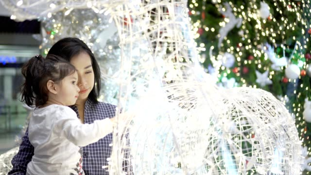 Mother and Daughter playing with light in Festive Christmas