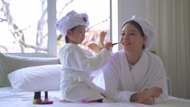 mother and daughter playing with makeup brushes in the bedroom - daughter stock videos & royalty-free footage