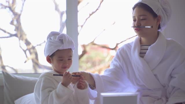 stockvideo's en b-roll-footage met mother and daughter playing with makeup brushes in the bedroom - in een handdoek gewikkeld