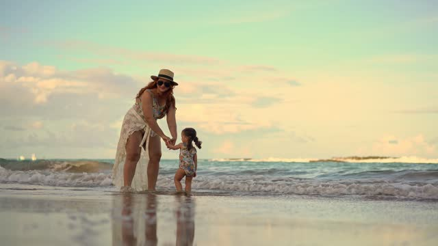 mother and daughter playing with sea foam - swimming costume stock videos & royalty-free footage