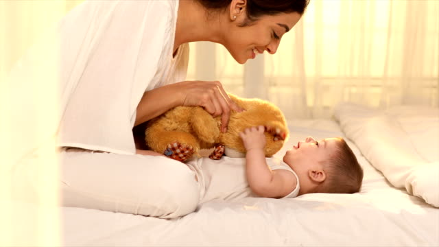 MS Mother and daughter playing with soft toy on bed/ Delhi, India