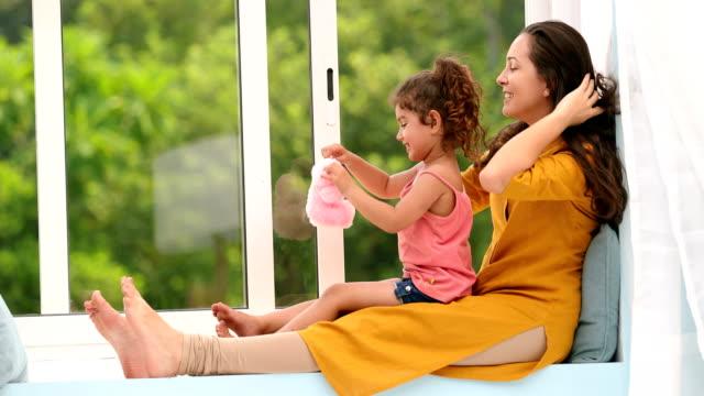 vídeos y material grabado en eventos de stock de ms mother and daughter playing with soft toy while sitting on window sill / chhatarpur, delhi, india - en el regazo