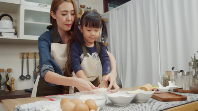 mother and daughter prepare bread dough in kitchen - daughter stock videos & royalty-free footage