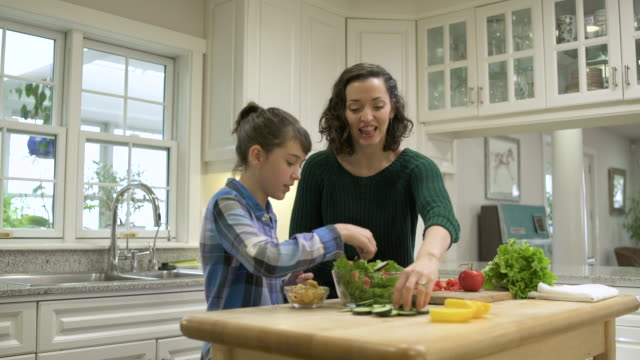 Mother and daughter preparing a bowl of salad