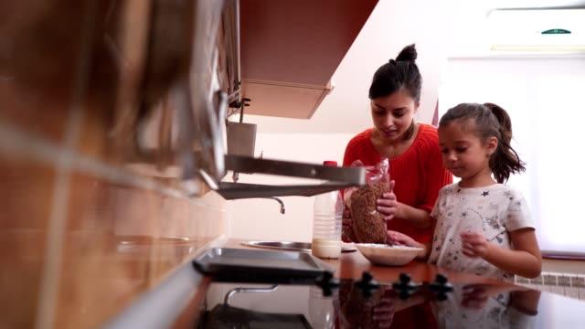 vidéos et rushes de mère et fille, prépare le petit déjeuner ensemble - nurse