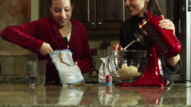 ms tu mother and daughter (8-9) preparing food in kitchen / orem, utah, usa - orem stock-videos und b-roll-filmmaterial