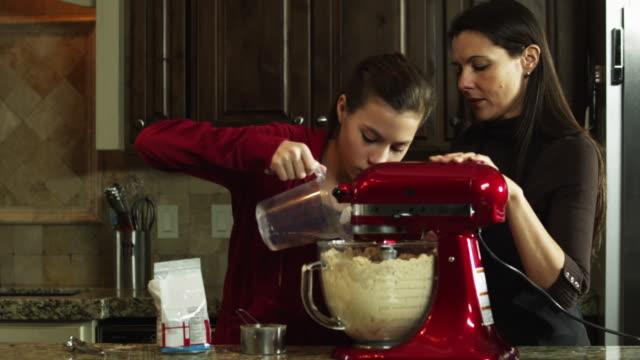 vídeos de stock, filmes e b-roll de ms mother and daughter (8-9) preparing food in kitchen / orem, utah, usa - orem utah