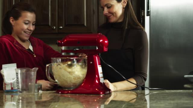 ms tu mother and daughter (8-9) preparing food in kitchen / orem, utah, usa - orem utah stock videos and b-roll footage