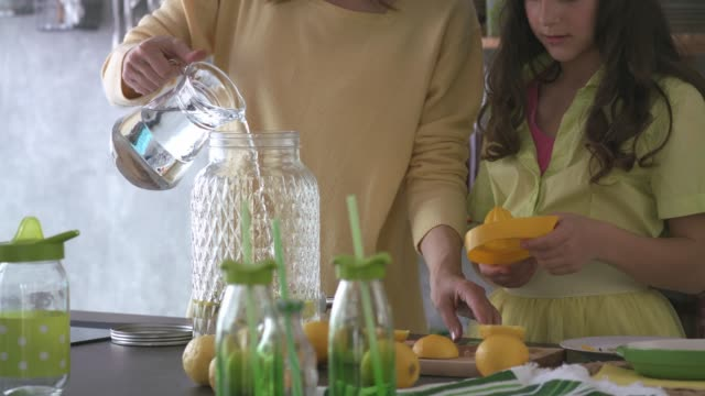 mother and daughter preparing tasty, refreshing lemonade together - pouring stock videos & royalty-free footage