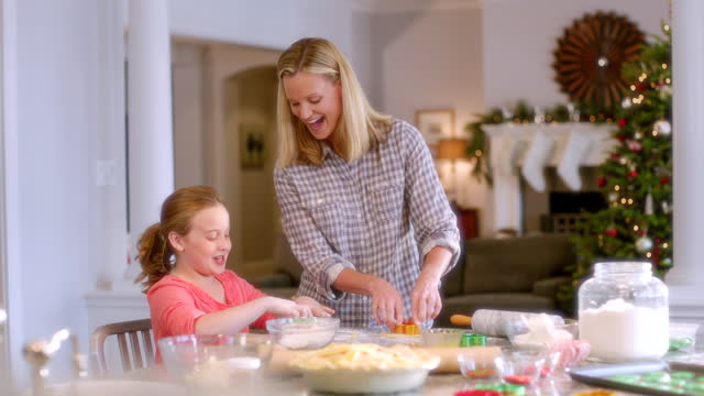 mother and daughter press christmas cookie-cutter shapes into cookie dough (dolly-shot) - moulding trim stock videos & royalty-free footage
