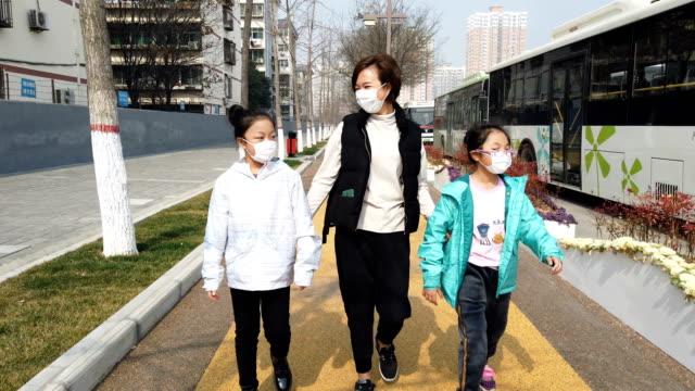 madre e figlia si proteggono dal coronavirus con le maschere - guanto indumento sportivo protettivo video stock e b–roll