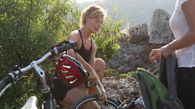 Mother and daughter pump bike tire, in hills
