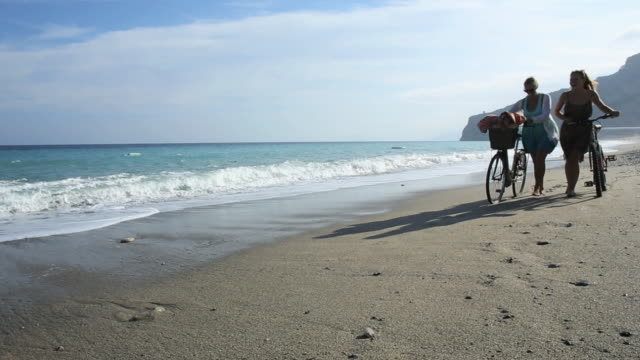 """""""mother and daughter push bikes along beach, surf edge"""" - track imprint stock videos & royalty-free footage"""