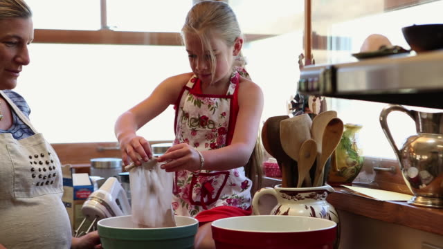 MS Mother and daughter putting power in bowl for baking in kitchen / Lamy, New Mexico, United States