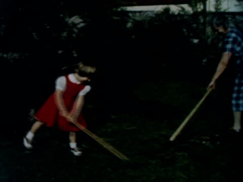 a mother and daughter rake grass in a back yard. - chores stock videos & royalty-free footage