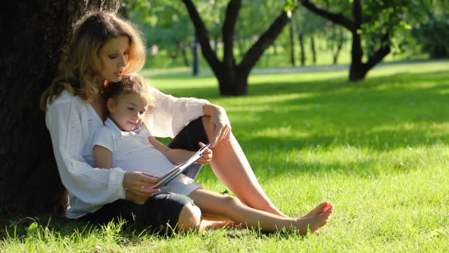 mother and daughter reading book in park - storytelling stock videos and b-roll footage