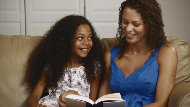 stockvideo's en b-roll-footage met ms pan mother and daughter (12-13) reading book on sofa / edmonds, washington state, usa - 12 13 jaar