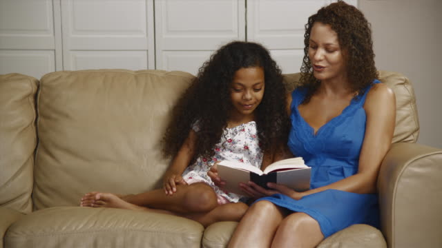 MS Mother and daughter (12-13) reading book on sofa / Edmonds, Washington State, USA