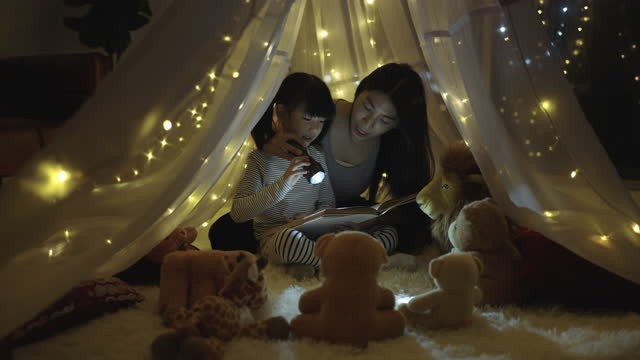 mother and daughter reading book with flashlight under the tent - bedroom stock videos & royalty-free footage