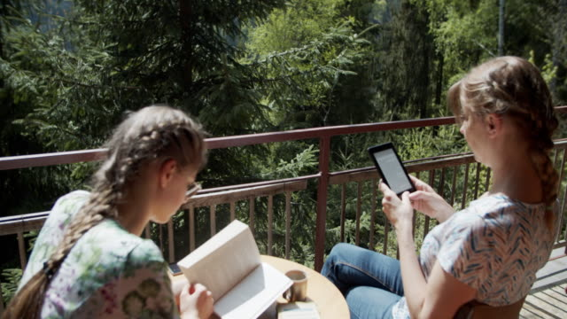 mother and daughter reading books on balcony - terrazza video stock e b–roll
