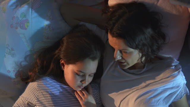 hd crane: mother and daughter reading in bed - storytelling stock videos and b-roll footage