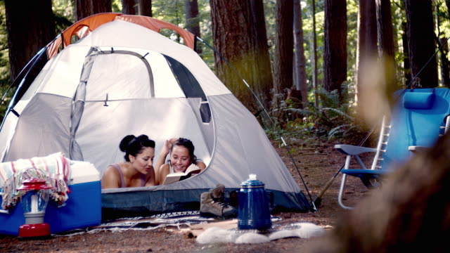 ms mother and daughter (14-15) reading in tent / lynnwood, washington state, usa - camping stock videos & royalty-free footage