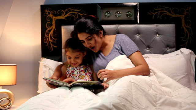 Mother and daughter reading storytelling book, Delhi, India