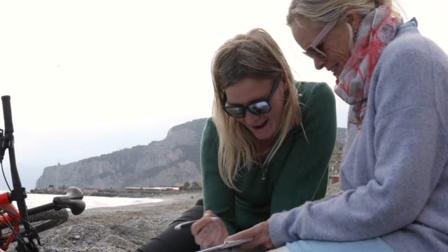 mother and daughter relax on beach, with writing tablet - pullover stock videos & royalty-free footage