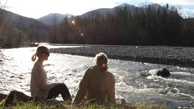 mother and daughter relax on riverbank together, talking - adult offspring stock videos & royalty-free footage