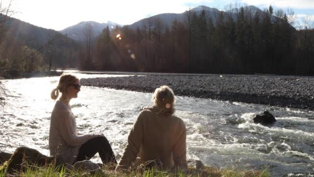 mutter und tochter entspannen gemeinsam am flussufer, reden - erwachsene kinder stock-videos und b-roll-filmmaterial