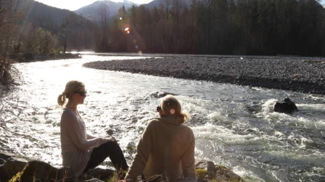 mutter und tochter entspannen gemeinsam am flussufer, reden - part of a series stock-videos und b-roll-filmmaterial