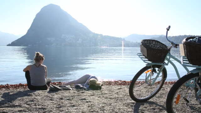 Mother and daughter relax with bicycles by lakeshore