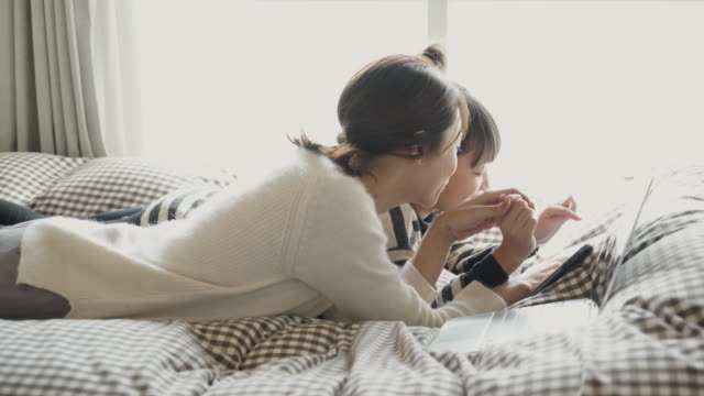 mother and daughter relaxing by phone and playing games in bed - communication点の映像素材/bロール